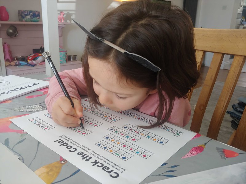 An image of a child filling out an Octokids activity sheet