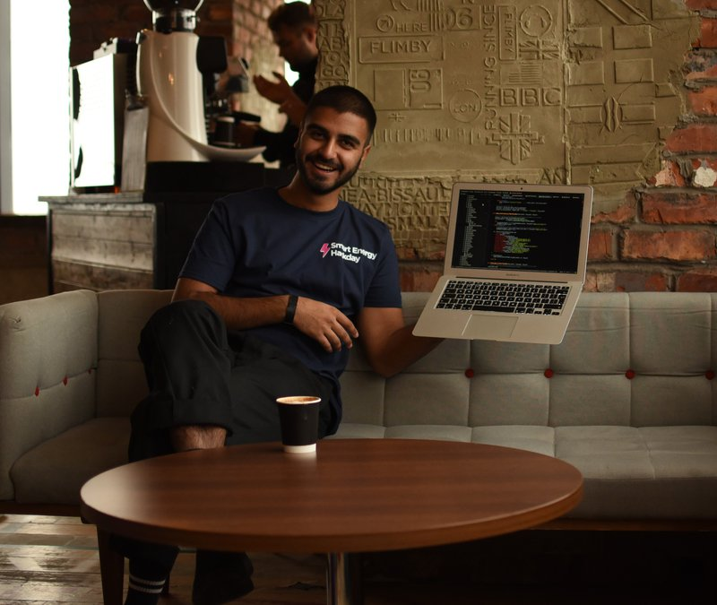A photo of Suraj holding up a laptop at the office