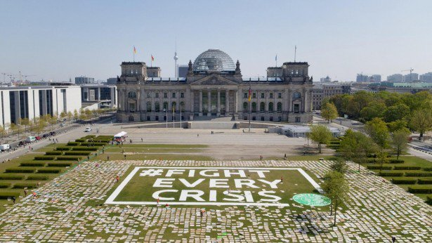 placards arranged outside a government building in Germany. They spell out 'Fight every Crisis'.