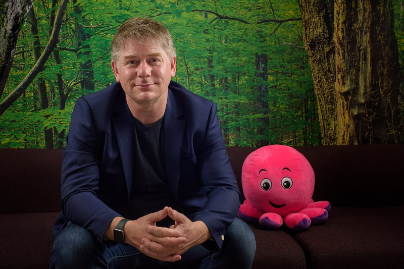 An image of Greg sitting on a sofa next to a pink cuddly octopus toy