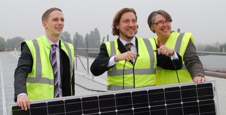 An image of three oxford community energy enthusiasts holding a solar panel on the roof their hq