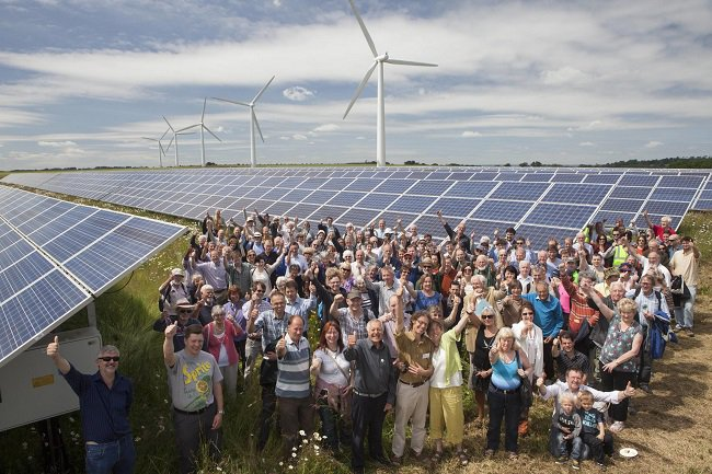 An image showing a group of community members standing amongst the solar panels and turbines at westmill