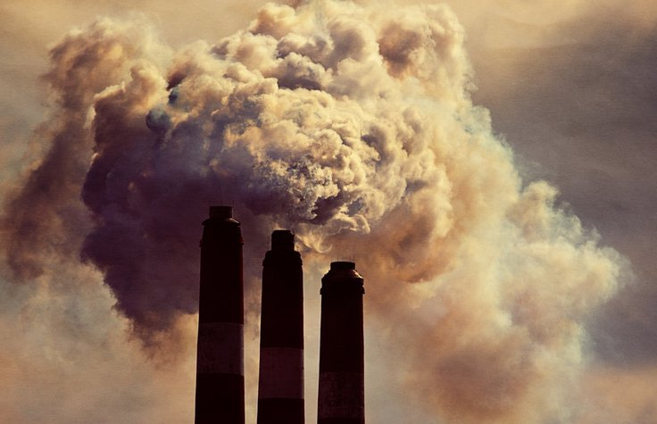 Image of three industrial chimneys billowing smoke
